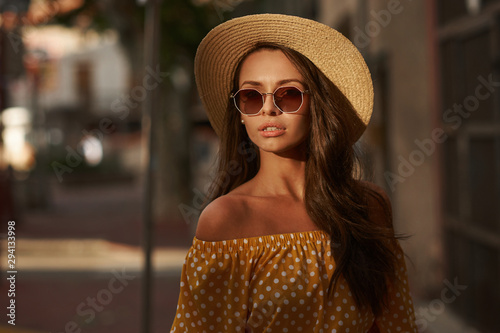 obraz dibond Closeup outdoor portrait of young beautiful caucasian young woman with long brunette hair wearing yellow polka dot dress, sunglasses and thatch hat. Summer sunny evening street
