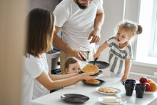 Hardworking Young Girl Helping Her Parents To Cook Pancakes. Close Up Photo