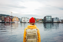 Back View Of Carefree Man Traveller With Touristic Rucksack Wearing Yellow Coat And Rad Hat Standing On Berth And Looking Toward Scandinavian City. Tourist Walking The Small Authentic City Among Ship