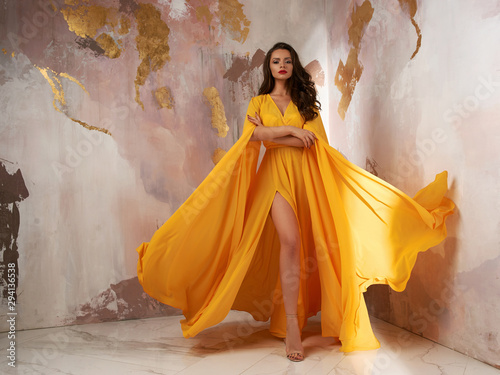 Foto Young beautful caucasian woman with long wavy brunette hair in yellow flying dress posing against wall