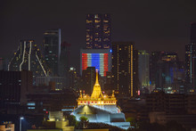 Golden Mount Or Wat Saket, Phukhao Thong, And Skyscraper Buildings With Thailand Flag At Night In Bangkok City, Thailand. Buddhist Temples.