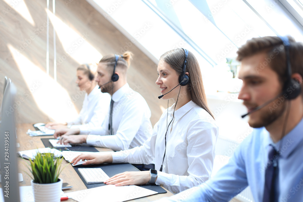 Fototapeta Female customer support operator with headset and smiling accompanied by her team.