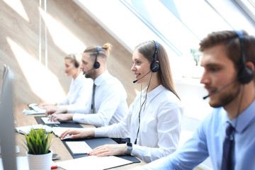 Obraz na SzkleFemale customer support operator with headset and smiling accompanied by her team.