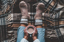 Cozy Woman In Knitted Winter Warm Socks And In Pajamas Holding A Cup Of Hot Cocoa During Resting On Checkered Plaid Blanket At Home In Winter Time. Cozy Time And Winter Drinks. Top View