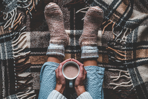 Obraz Cozy woman in knitted winter warm socks and in pajamas holding a cup of hot cocoa during resting on checkered plaid blanket at home in winter time. Cozy time and winter drinks. Top view - fototapety do salonu