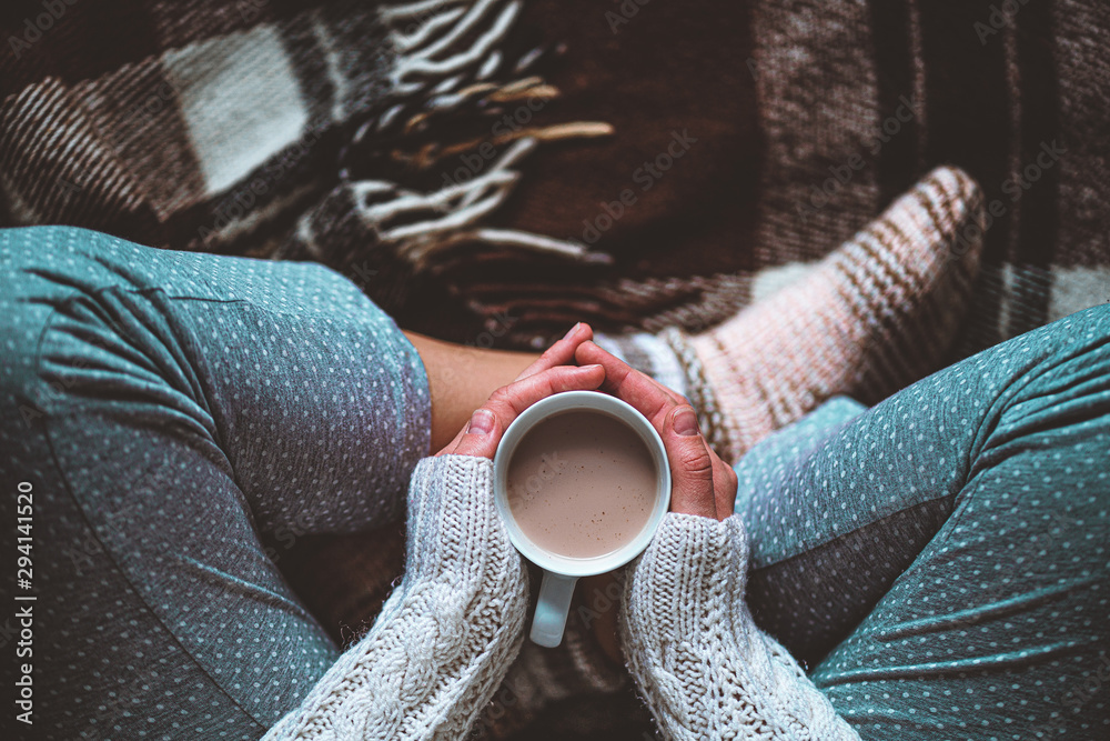 Fototapeta Cozy woman in knitted winter warm socks and in pajamas holding a cup of hot cocoa during resting on checkered plaid blanket at home in winter time. Cozy time and winter drinks. Top view