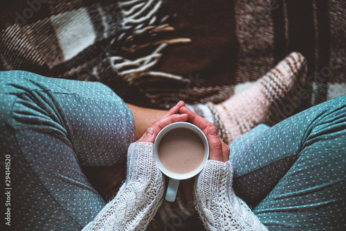 Cozy woman in knitted winter warm socks and in pajamas holding a cup of hot cocoa during resting on checkered plaid blanket at home in winter time Tableau sur Toile