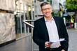Smiling senior businessman in glasses holding a document and looking at the camera - Image