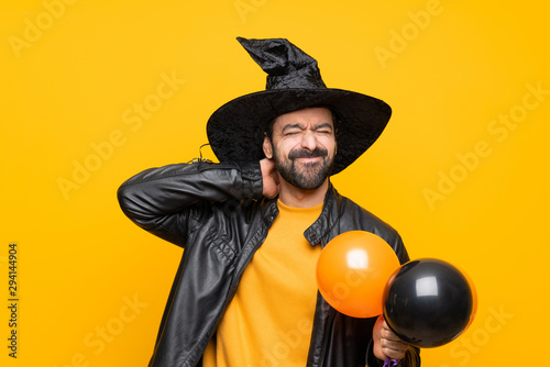 Fotografia  Man with witch hat holding black and orange air balloons for halloween party wit