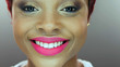 Close-up detail of an African American woman smiling over gray background