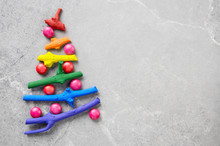 Flat Lay Stylized Christmas Tree Made Of Small Twigs Painted In Rainbow Colors On Stone Background. Space For Text