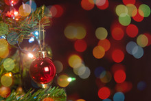 Christmas Decoration. Hanging Red Balls On Pine Branches Christmas Tree Garland And Ornaments Over Abstract Bokeh Background With Copy Space.