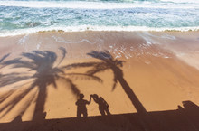 Pristine Tropical Beach With Shadows From Palm Trees And Happy Couple On The Sand.