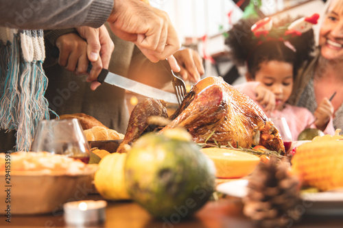 Thanksgiving Celebration Tradition Family Dinner Concept.family having holiday dinner and cutting turkey.Young black adult woman and her daughter happy.. - 294153593