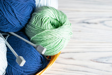 Knitting Hobby Composition With Blue And Green Yarn And Needles On White Wooden Background.