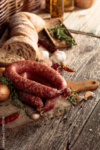 Photo  Dry-cured sausage with bread and spices on a old wooden table.