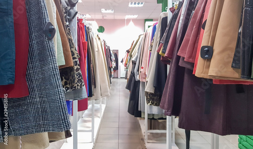 Photo Clothes hanging on shelves in a designer clothing store
