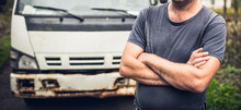 Male Driver In Old-fashioned T-shirt Has Crossed Hands And Stays Near His Old Rusty Truck On The Parking Place.