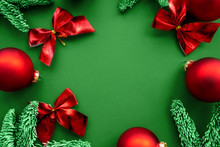 Beautiful Christmas Composition Of Red Balls And Bows That Decorate Sprigs Of Spruce On A Green Background, Place For Your Text. Holiday Concept.