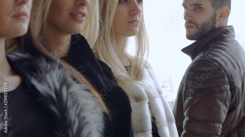 A young bearded man looks at three women in expensive furs and turns away from them Fototapet