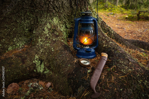 Knife, compass and gasoline lantern standing on a ground in the deep forest Canvas Print