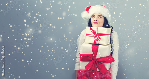 Fotografie, Tablou  Young woman with santa hat holding gift boxes on a gray background