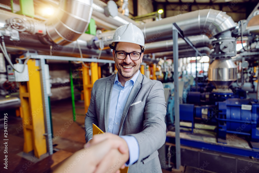 Fototapeta Handsome caucasian manager in suit and with helmet on head holding folder with documents and shaking hands with investor while standing in power plant.