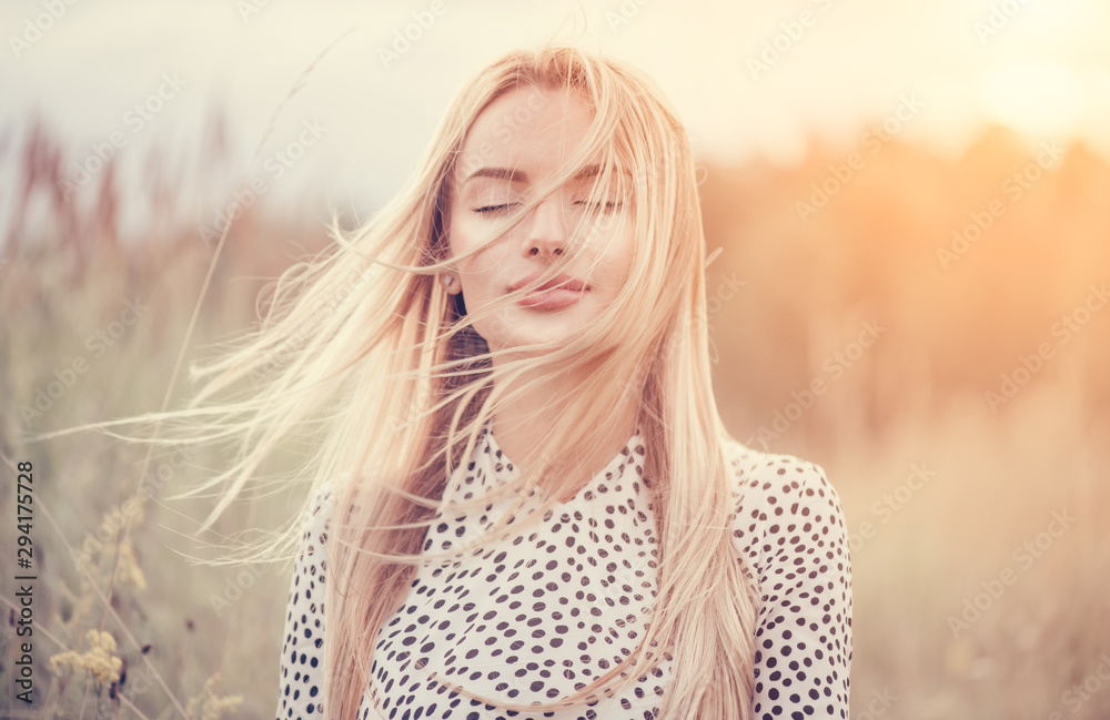 Obraz Close Up Portrait of beauty girl with fluttering white hair enjoying nature outdoors, on a field. Flying blonde hair on the wind. Breeze playing with girl's hair. Beautiful young woman face closeup. fototapeta, plakat