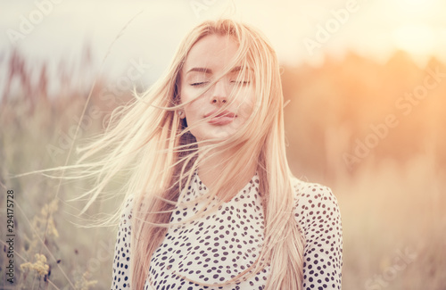Obraz Close Up Portrait of beauty girl with fluttering white hair enjoying nature outdoors, on a field. Flying blonde hair on the wind. Breeze playing with girl's hair. Beautiful young woman face closeup. - fototapety do salonu