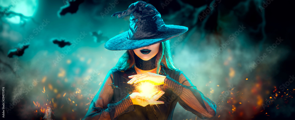 Fototapeta Halloween Witch girl with making witchcraft, magic in her hands, spells. Beautiful young woman in witches hat conjuring. Spooky dark magic forest background. Magician. Wide Halloween party art design