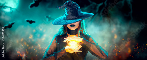 Halloween Witch girl with making witchcraft, magic in her hands, spells. Beautiful young woman in witches hat conjuring. Spooky dark magic forest background. Magician. Wide Halloween party art design - 294175976