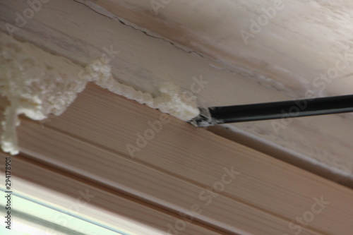inaccurate apply a polyurethane foam from a gun on the wooden window opening Wallpaper Mural