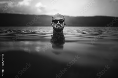 Fotografiet  Brutal bearded man in sunglasses emerge in lake waves