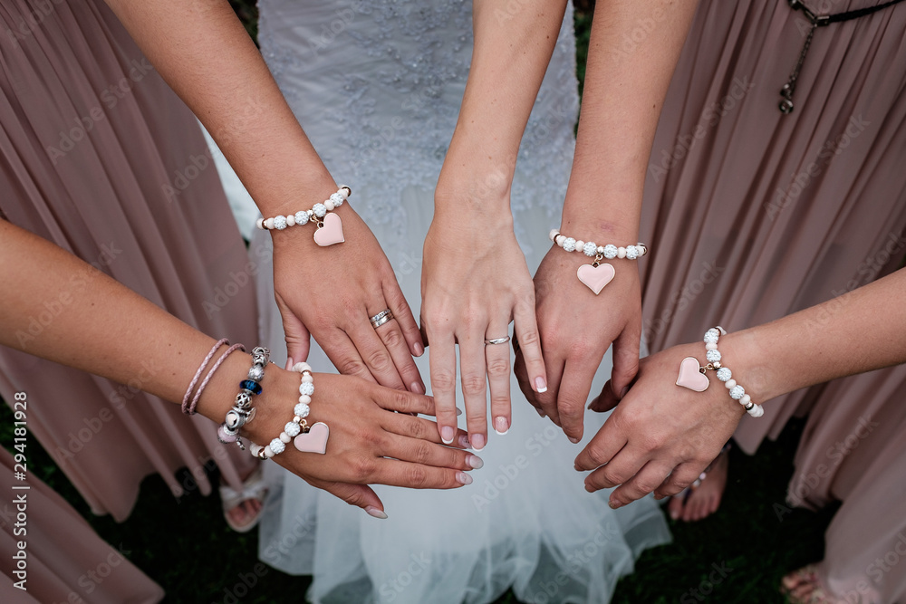 Fototapeta Four woman's hand with heart bracelet