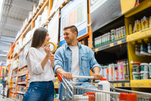 Obraz Couple with a cart buying building materials - fototapety do salonu