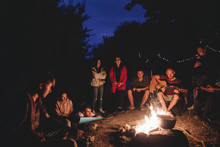 Hipster Man Playing On Acoustic Guitar And Singing Song With Friends Travelers At Big Bonfire At Night Camp In The Forest. Group Of People Chilling At Fire In The Evening, Camping Near Lake
