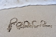 Close Up Background  With Peace Written In The Sand With Ocean Wave Foam