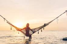 Girl Relaxing In Hammock On Sunset Beach