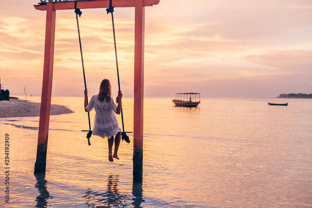 Fototapeta Girl relaxing in swings on sunset beach