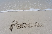 Horizontal Background With Peace Written In The Sand With A Ocean Wave