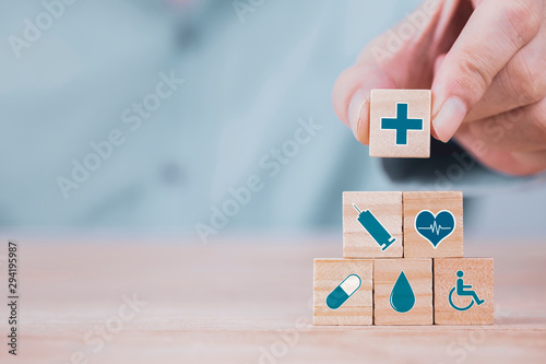 Stampa su Tela  Businessman chooses a emoticon icons healthcare medical symbol on wooden block ,