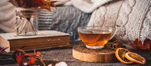 Cozy Autumn Or Winter At Home. A Cup Of Tea, Autumn Casts A Book A Garland On A Wooden Table Near A Bed With Warm Plaids. Lifestyle Autumn Hygge Lagom?concept Of A Holiday And Autumn Weekend.Banner