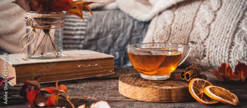 Spoed Foto op Canvas Thee Cozy autumn or winter at home. A cup of tea, autumn casts a book a garland on a wooden table near a bed with warm plaids. Lifestyle autumn hygge lagom?concept of a holiday and autumn weekend.Banner