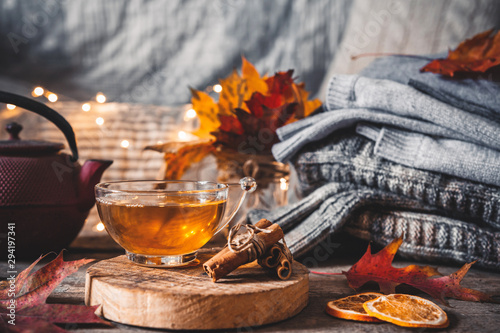 Photo Stands Tea Cozy autumn or winter at home. A cup of tea, autumn casts a book a garland on a wooden table near a bed with warm plaids. Lifestyle autumn hygge lagom?concept of a holiday and autumn weekend.
