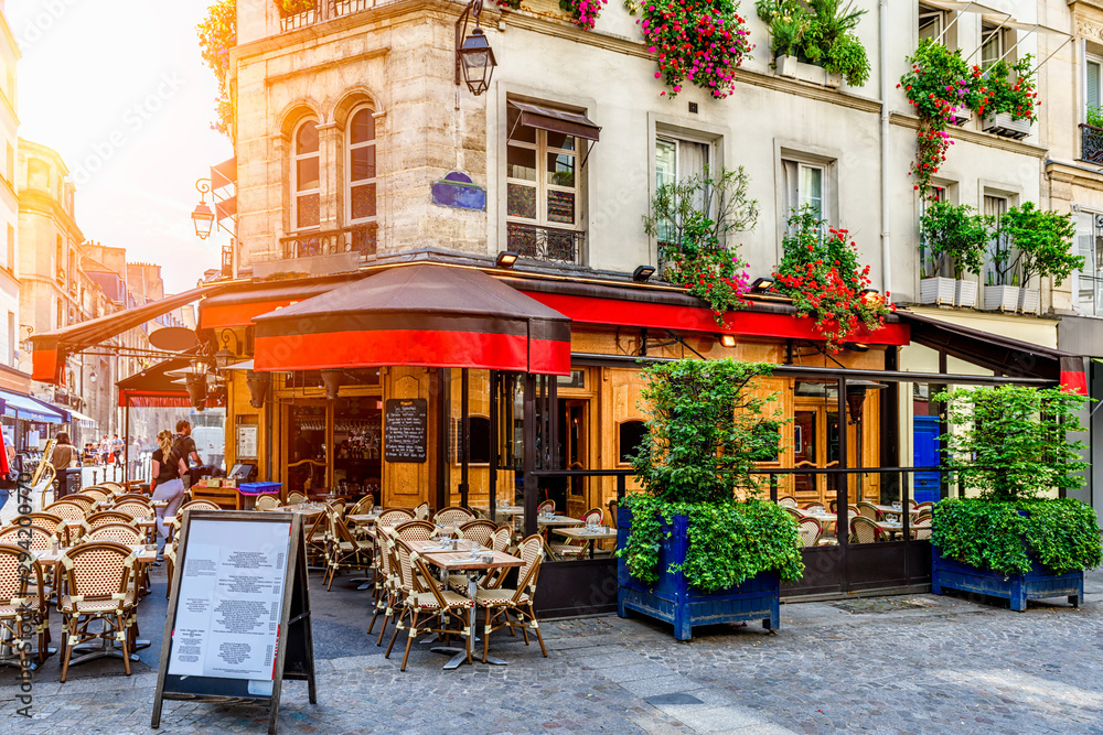 Fototapeta Cozy street with tables of cafe in Paris, France. Architecture and landmark of Paris. Cozy Paris cityscape.