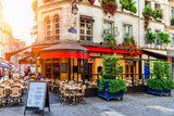 Fototapeta Uliczki - Cozy street with tables of cafe in Paris, France. Architecture and landmark of Paris. Cozy Paris cityscape.