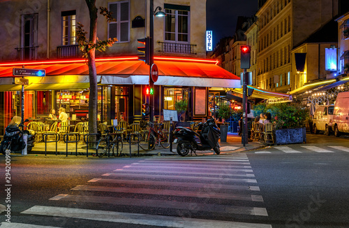 Obraz na plátně Boulevard San-German with tables of cafe in Paris at night, France