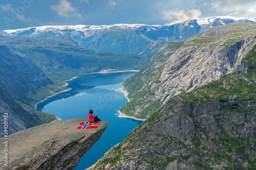 Foto auf Gartenposter Blau Jeans Trolltunga rock, mountain lake Ringedalsvatnet landscape, Norway. Girl sitting on the cliff with Norwegian flag,