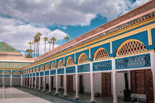 Landscape view of the centre area of the palace, built in traditional form with many decorations. Sky and palm trees in the background Marrakech, Morocco.