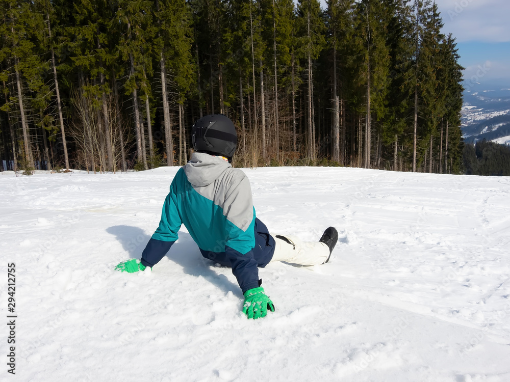 Fototapety, obrazy: Guy snowboarder sitting in the snow and resting after skiing